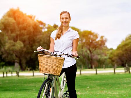 Beautiful young blonde woman with bike in park Stok Fotoğraf
