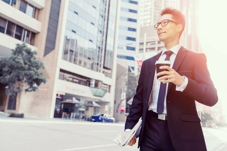 Businessman with coffee in a city