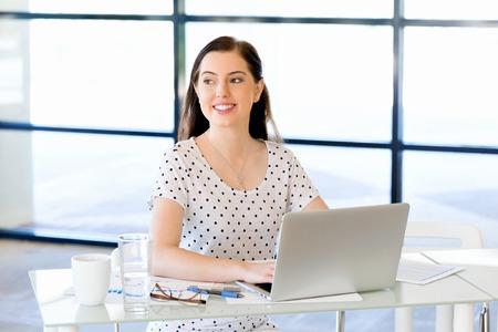 Portret van onderneemster die bij computer in bureau werkt