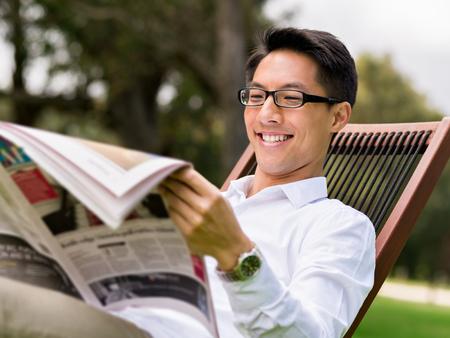 ビジネスの男性が公園で新聞を読む 写真素材