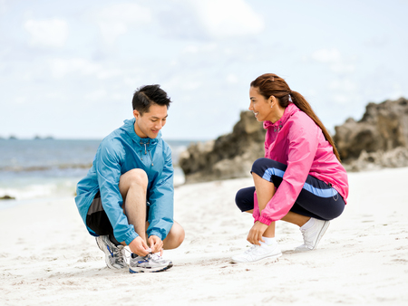 Young couple of runners tying shoelace at the seaside Stock Photo