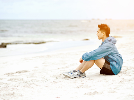 voyage: Young man sitting at the beach in sportswear Banque d'images