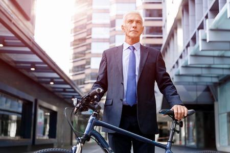 Successful businessman riding bicycle Stock fotó - 87428866