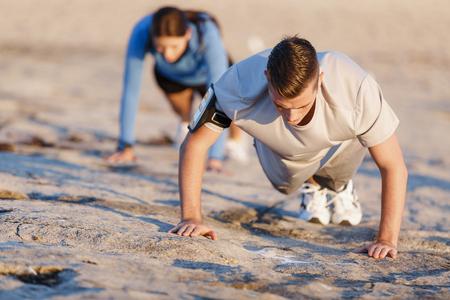 Jong koppel doet push ups op oceaan strand