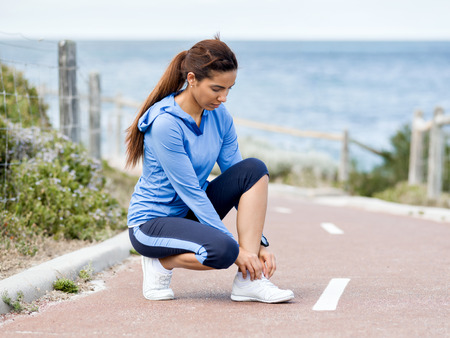 Woman runner tying shoelace at the seaside Stock Photo - 87565178