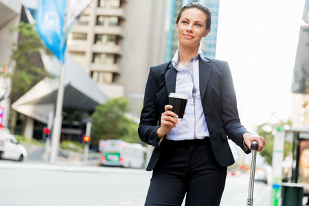 Bedrijfsvrouw die koffer trekken die in stad lopen Stockfoto