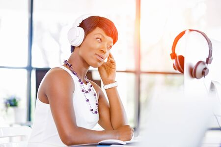 african business: Young beautiful businesswoman listening music in headphones Stock Photo