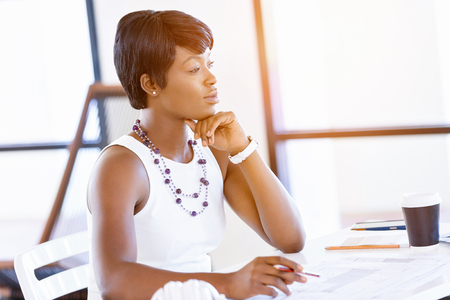 designer: Young woman sitting at a desk in an office and working on blueprint