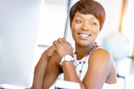 african business: Young businesswoman sitting at desk and working