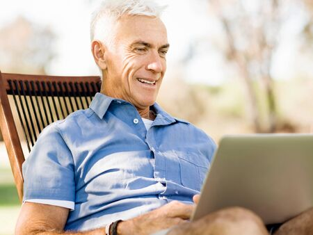 Senior man with notebook sitting in the park Stock Photo