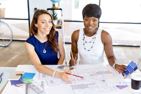 designer: Young women sitting at a desk in an office and working on blueprint
