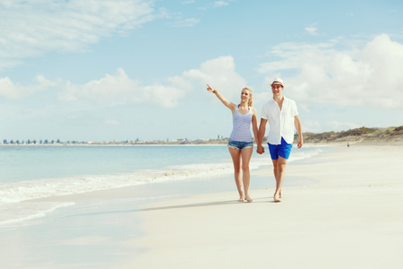 stroll: Romantic young couple on the beach