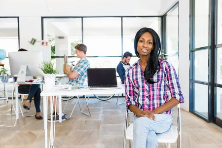 designer: Portrait of smiling afro-american office worker in offfice with her colleagues Stock Photo