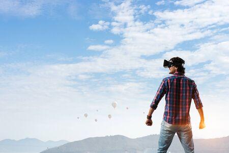 Man in virtual helmet . Mixed media Imagens