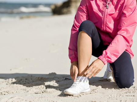 Woman runner tying shoelace at the seaside Stock Photo