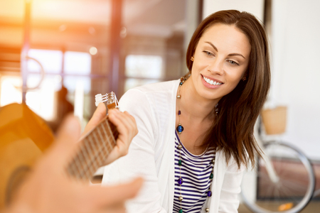 Young woman in office with friend playing guitar