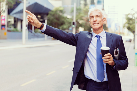 Businessman catching taxi in city Stock Photo
