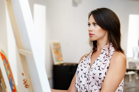 Young caucasian woman standing in art gallery front of  paintings Stock Photo