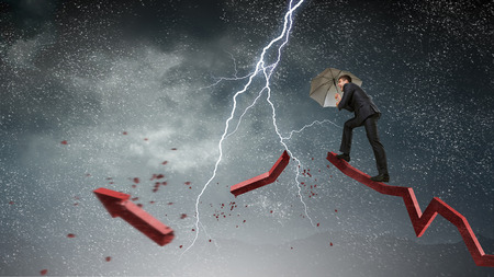 Businessman protects himself from the crisis. Mixed media Stock Photo