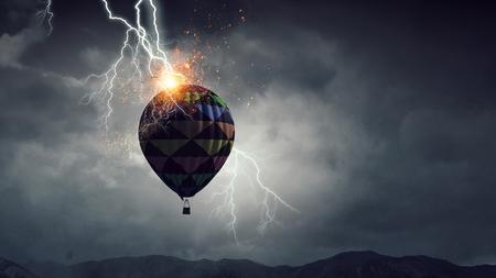Lightning striking color aerostat in dark sky. Mixed media