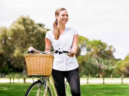 公園では自転車の若い金髪美女 写真素材