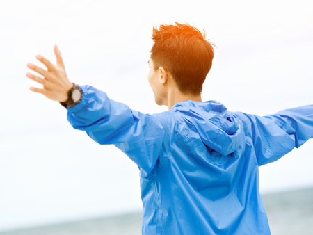 Young man with outstretched arms at the beach