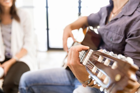 Young man playing the guitar in office 版權商用圖片