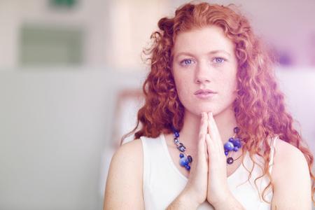 Closeup portrait of a young woman praying