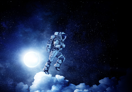 Spaceman run on clouds. Mixed media Stock Photo