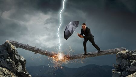 Businessman with black umbrella. Mixed media Stock Photo