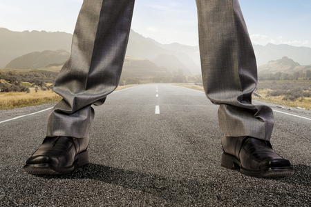 Legs of giant businessman standing on asphalt road. Mixed media Stock Photo - 89022700