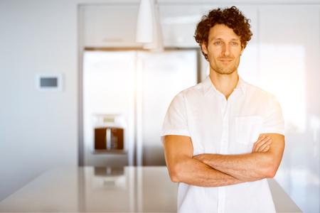 Portret van een slimme jonge man die in de keuken