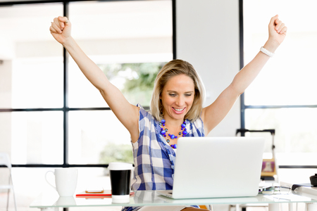 One young woman in office celebrating success