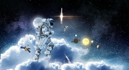 Spaceman run on clouds. Mixed media Reklamní fotografie
