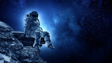 Spaceman on rock edge. Mixed media Stok Fotoğraf