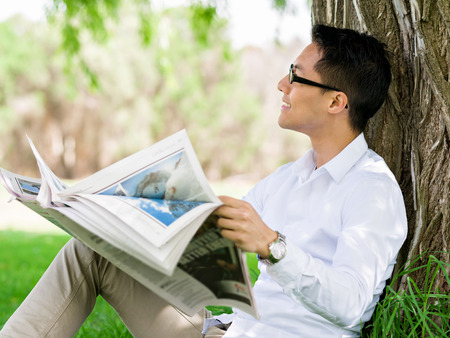 editor: Business man reading a newspaper in park Stock Photo