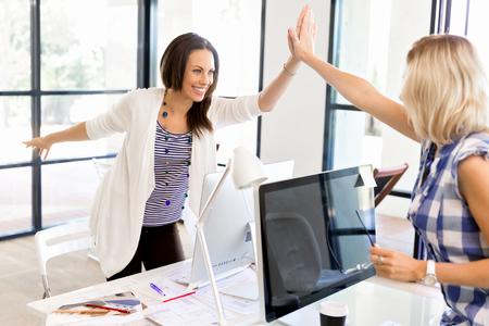성공을 축하하는 사무실에서 두 젊은 여성