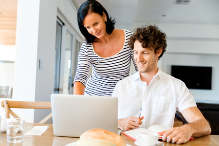 Happy modern couple working on laptop at home Stock Photo