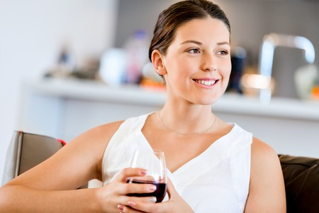 Beautiful young woman holding glass with red wine