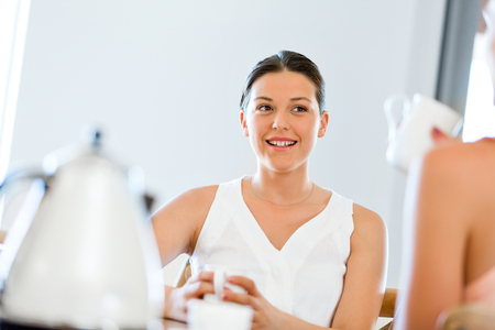 Young woman with her friend having tea at home Stock Photo - 89499030