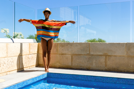 Young woman standing next to swimming pool