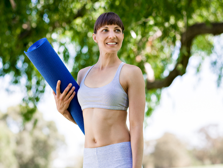 Young woman witth a gym mat in the park Stock Photo