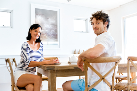 Couple sitting at home and chatting Imagens