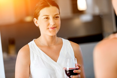Young woman with her friend holding a glass of wine indoors Stock Photo