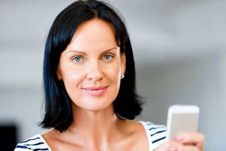 house call: Portrait of attractive woman holding phone