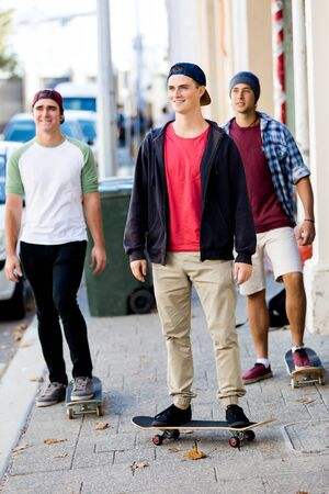 Teenage friends walking at the street with skateboards