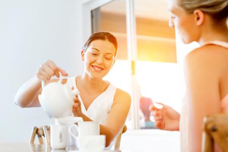 Young woman with her friend having tea at home Stock Photo