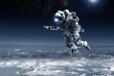 Astronaut floating above clouds Stock Photo
