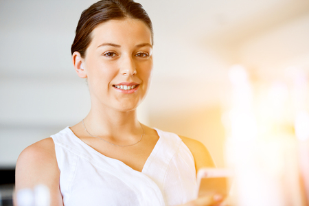Portrait of young woman holding phone