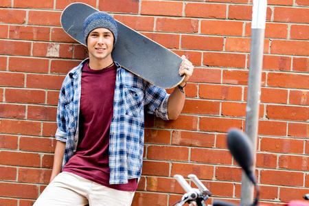 Adolescente con patineta de pie junto a la pared